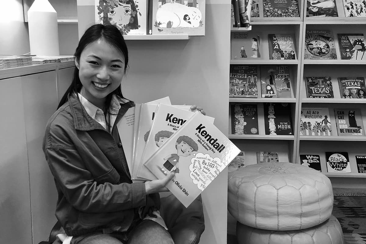 Liv Shin holding up a copy of her children's book, Kendall: A Story of a Young Boy with Autism