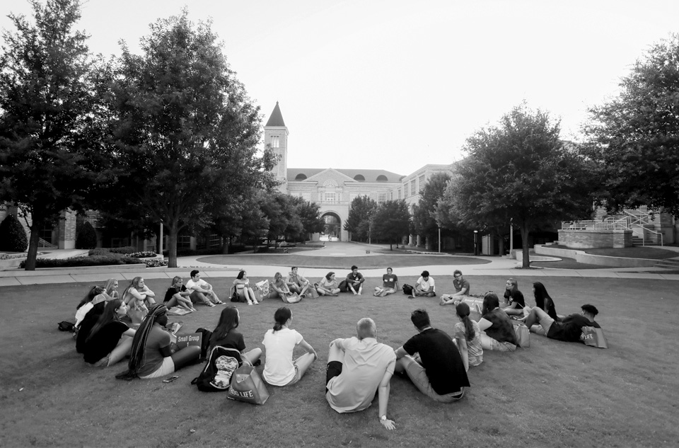 A group of students sitting in a circle on the campus lawn